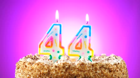 gênero alimentício : Birthday cake with a burning birthday candle. Number 44. Background changes color