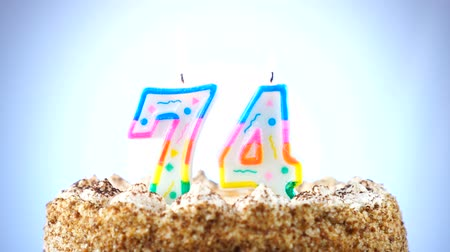 gênero alimentício : Birthday cake with a burning birthday candle. Number 74. Background changes color Stock Footage