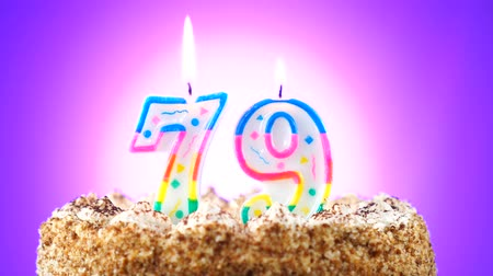 gênero alimentício : Birthday cake with a burning birthday candle. Number 79. Background changes color
