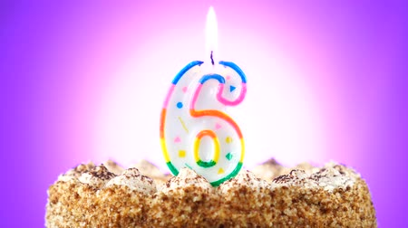 seis : Birthday cake with a burning birthday candle. Number 6. Background changes color