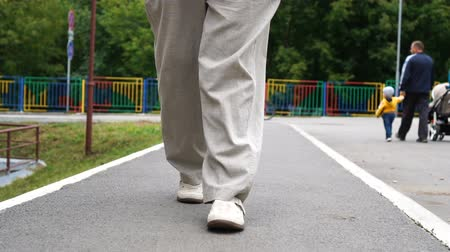 kostka : Man legs in white shoes walking on tile road outdoors