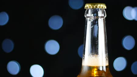 pálido : Cold beer in a clear bottle rotating on a black background with bright lights