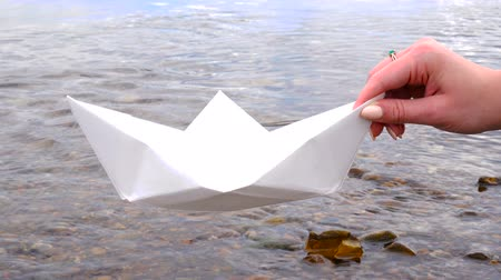 оригами : Womans hand holding paper boat over the river Стоковые видеозаписи