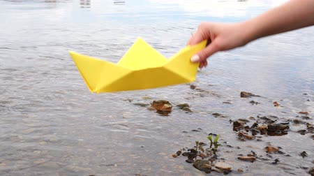 оригами : Womans hand holding yellow paper boat over the river Стоковые видеозаписи