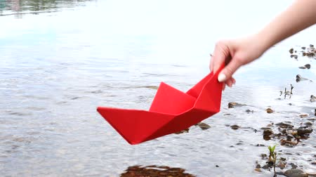оригами : Womans hand holding red paper boat over the river and playing with him