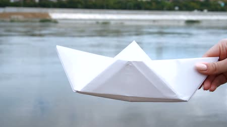 оригами : Womans hand holding white paper boat over the river