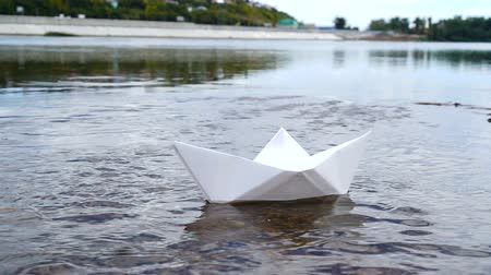 оригами : Womans hand putting white paper boat on the water and pushing it away.
