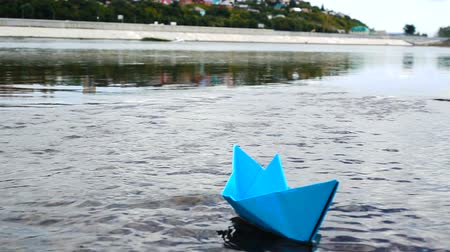 оригами : Womans hand putting blue paper boat on the water and pushing it away