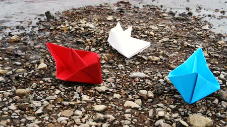 оригами : On the Beach - Three colorful paper boats on a stone dune near of beautiful azure sea or river on a sunny day