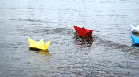 оригами : Four multicolored paper boats sailing on water on romantic sunset. Origami.