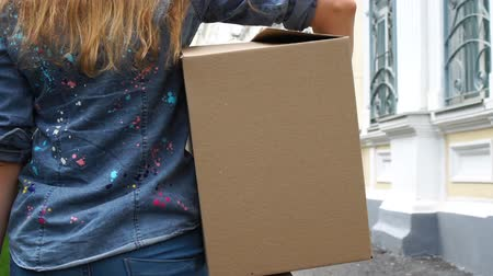 relocate : Back view of woman carrying a cardboard box and walking outdoor