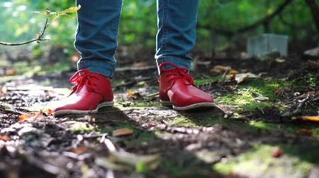 red shoes : Female feet in red sneakers at beautiful green forest
