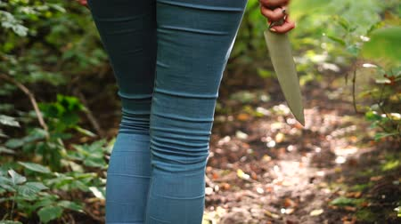 goes : Woman with knife in her hand goes through green scary forest. Protective or criminal content.