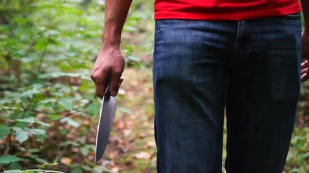 dýka : Unrecognizable man walking through green forest and holding knife. Sense of danger.