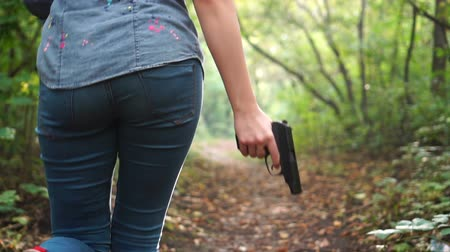 vengeance : Woman running through green scary forest and holding gun. Sense of danger. Protective or criminal content.
