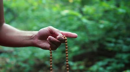 tespih : Prayer beads in hand. Male hand holding rosary, praying to god on green nature background, religious spirituality.