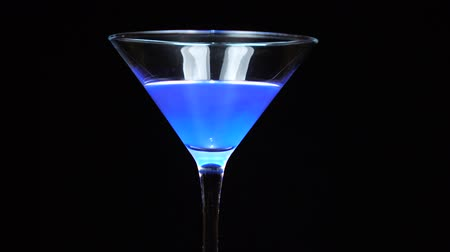 martini glasses : Blue cocktail being poured into a martini cocktail glass