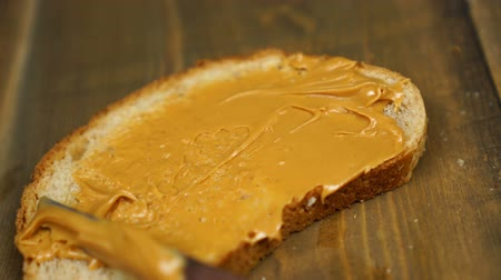 dilis : Man makes a peanut butter sandwich. Male hands spreading butter on bread in kitchen