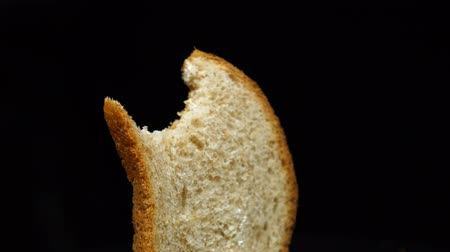 потреблять : Bitten slice of the toast bread rotates, isolated over the white background