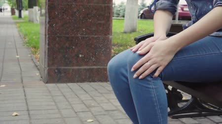 osteoarthritis : Woman standing up from bench feeling sharp knee pain in park, osteoarthritis, injury Stock Footage