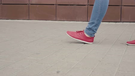 paving : Close up of womans legs in red sneakers. Stock Footage