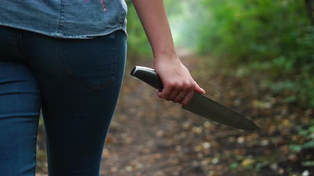 overval : Woman with knife in her hand goes through green scary forest. Protective or criminal content
