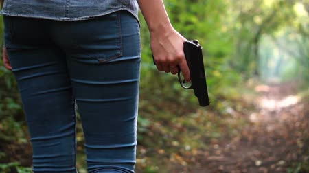 goes : Woman walking through green scary forest and holding gun. Sense of danger. Protective or criminal content.