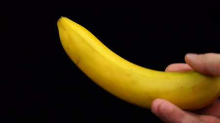 banan : Male hand holds an banana on a black background Wideo