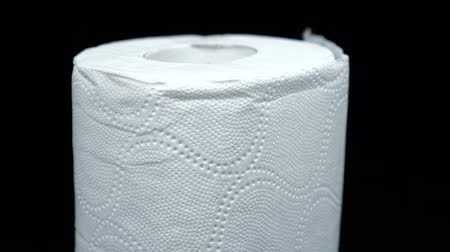 уборная : Roll of white toilet paper rotates in front black background Стоковые видеозаписи