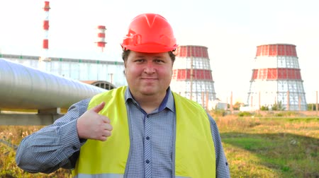 petrolkémiai : Worker or engineer looking directly at the camera and showing thumb up standing in front of a power station