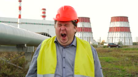 нефтехимический : Tired worker, engineer, or electrician fall asleep, yawning, standing in front of a power station Стоковые видеозаписи