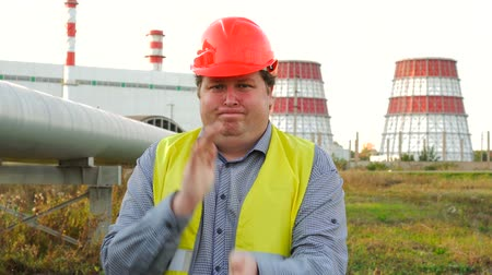 petroleum refinery : Worker, engineer, or electrician looking at the camera and shaking off dust from his hands in front of a power station Stock Footage