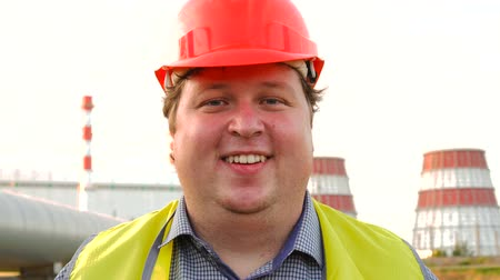 hardhat : Happy worker, engineer, or electrician looking directly at the camera and winking in front of a power station
