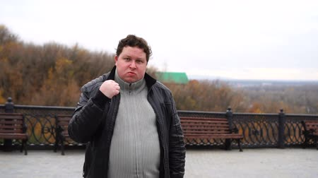 ameaça : Zoom in portrait of fat angry man looking at camera and threatens with a shaking fist outdoor.