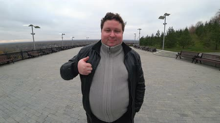 пухлый : Wide angle lens: young fat man looking at camera and showing thumb up