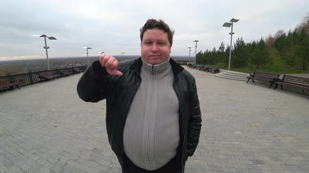 пухлый : Wide angle lens: young fat man looking at camera and showing thumb down