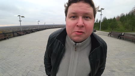 comediante : Wide angle lens: young fat man noticed hidden camera and looks in it