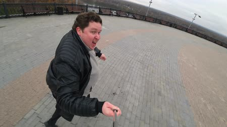 hajtások : Fat man running in city. Man shoots himself on the action camera using selfie-stick. Wide-angle lens