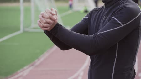 cabeça e ombros : Theme sport and health. Young Caucasian male athlete runner doing warm up, warming up stretching arm muscles before training at the city stadium, treadmill track. Stock Footage