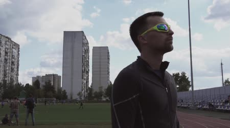 self made : March 2, 2019. Theme sport and health. Portrait of a young caucasian man in sportswear and sunglasses. Training sports lesson at city stadium track treadmill. Runner jogging outdoors.