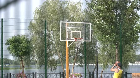 March 11, 2019. Ukraine, Kiev. An adult male of middle age plays basetol alone, throws the ball in a basketball ring on a sunny day. Stock Footage