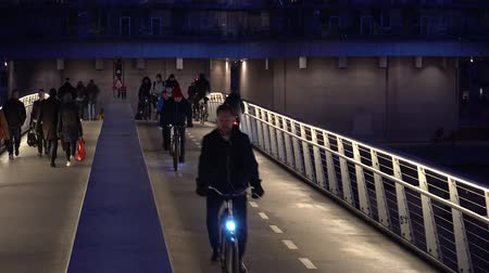 corrimão : February 18, 2019. Denmark, Copenhagen. The pedestrian bridge is divided into two parts: a bicycle road and a hiking path. City night view with highlight. Ecological view of transport bike in Europe.