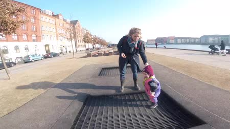 February 18, 2019. Denmark, Copenhagen.adult person rejoices like child. Playground trampoline in ground, children trampoline, springs throws people up funl. Woman jumping on street trampoline. Stock Footage