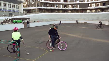 póló : March 17, 2019. Ukraine, Kiev. Bike polo game. group of people team on city bikes are training playing team game in stadium. man on bicycle with stick in his hands kicks ball into the goal.