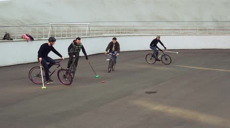 hokej : March 17, 2019. Ukraine, Kiev. Bike polo game. group of people team on city bikes are training playing team game in stadium. man on bicycle with stick in his hands kicks ball into the goal.