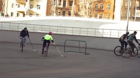 March 17, 2019. Ukraine, Kiev. Bike polo game. group of people team on city bikes are training playing team game in stadium. man on bicycle with stick in his hands kicks ball into the goal.