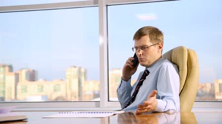 businessman talking on the phone in the office on the background of the city