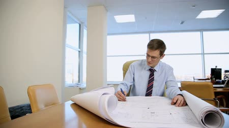 businessman architect of the drawings in his office