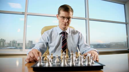 businessman in his office on the background of a large window playing chess