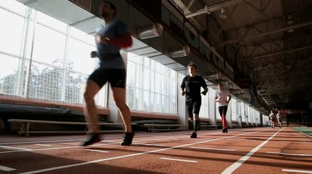 group of young people running around in the hall on the track Stock Footage